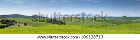 Tuscany landscape made of meadows,  green hills and the Amiata mountain far in the distance - stock photo