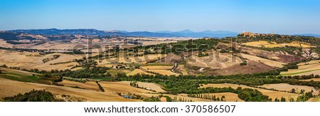 Tuscany landscape panorama with Pienza town on the hill, Italy. Cypress tree on the typical white road.  - stock photo