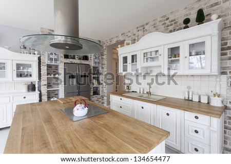 Tuscany - white kitchen shelves and silver refrigerator - stock photo