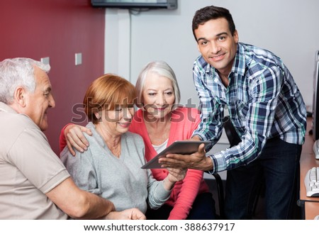 Tutor Guiding Senior Students To Use Digital Tablet In Classroom - stock photo