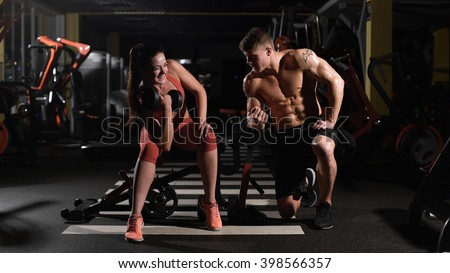 tutorship. Gym woman push-up strength pushup with dumbbell in a fitness workout encourages her comrade - stock photo