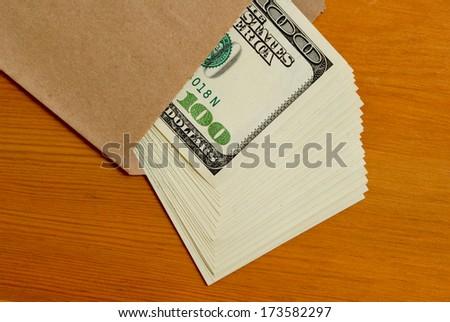Tutu dollars in cash in a paper envelope. - stock photo