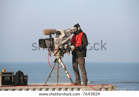 TV camera man filming a sports match - stock photo
