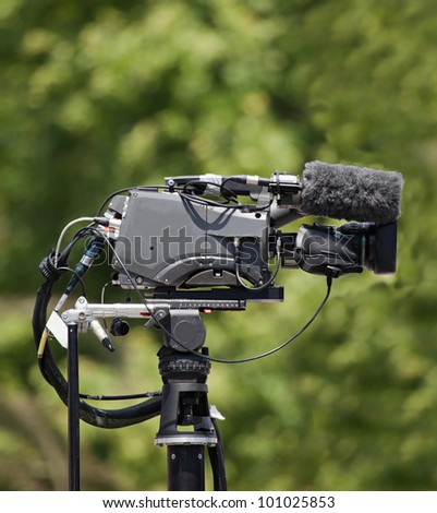 TV camera with green background - stock photo