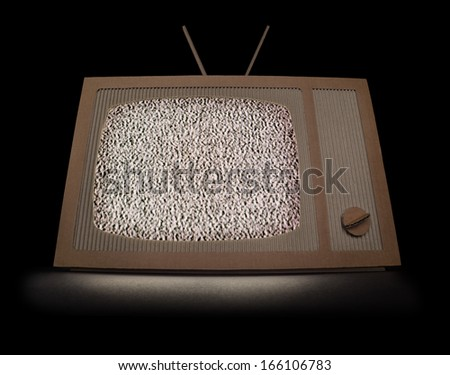 TV made of cardboard with white noise on a screen. Isolated on black. - stock photo