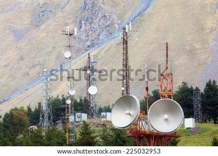 TV, radio and internet communications base in mountain, parabolic satellite antennas - stock photo