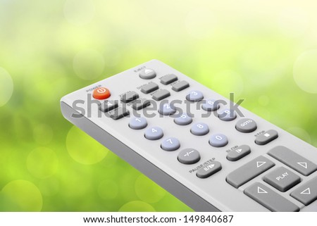 TV remote control on green bokeh - stock photo