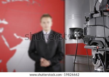 TV studio with video camera and unrecognizable presenter - stock photo