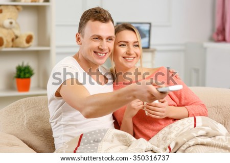 TV time. Young couple is drinking tea and using remote control to switch channels on the TV. - stock photo