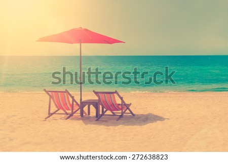 Tw lounge chairs and a sunshade umbrella on the beach - stock photo