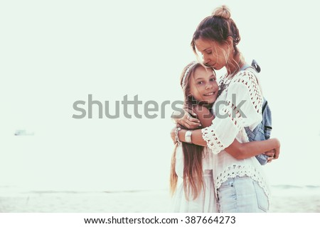 Tween daughter hugging with her mom, boho oriental style - stock photo