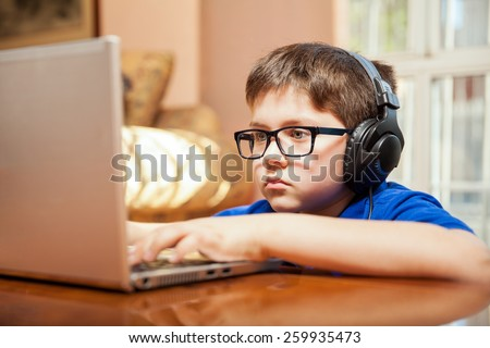Tween gamer wearing glasses and headphones playing a videogame on a laptop - stock photo