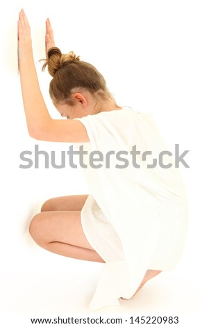 Tween girl in white dress against a white wall alone. - stock photo