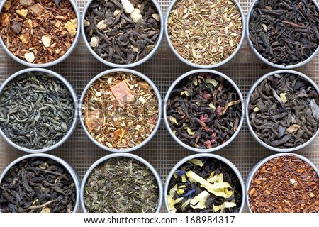 Twelve different teas in small metal pots arranged on a screen background. - stock photo