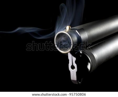 Twelve gauge shotgun that has blue smoke around its barrel - stock photo