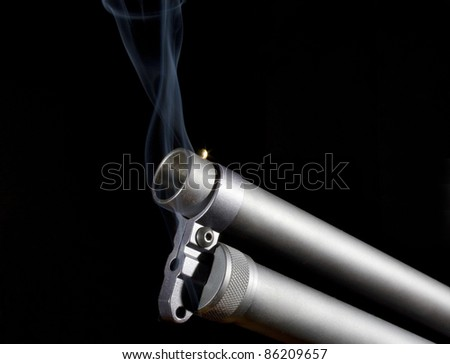 Twelve gauge shotgun that has smoke coming from its barrel - stock photo