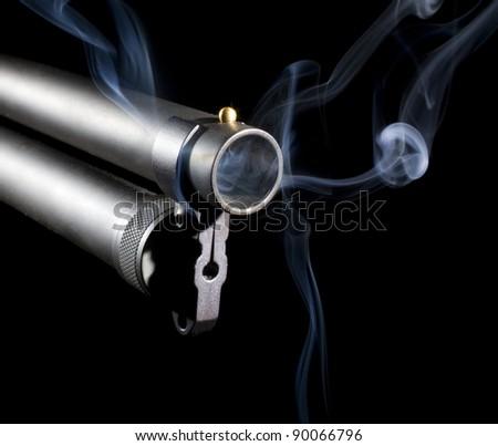 Twelve gauge shotgun with smoke coming from its barrel - stock photo