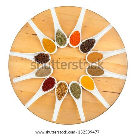 Twelve spices on white background - stock photo