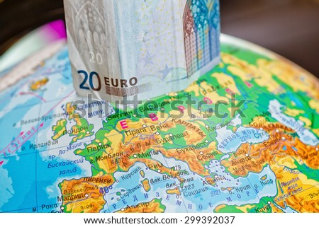 Twenty Euro banknote is worth on the globe next to Europe - stock photo