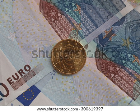 Twenty Euro (EUR) banknotes useful as a background or money concept - with a Fifty Euro coin from Vatican bearing the portrait of Pope Bergoglio Francis I - stock photo