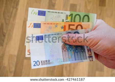 Twenty, fifty and one hundred euro bank-notes in white man hand. Pay bills with money. Currency concept. European currency. Money in hand - stock photo