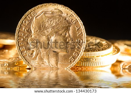 Twenty French Francs gold coins with water reflections - stock photo