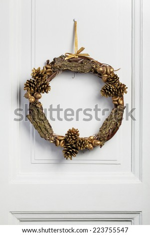 Twig wreath of dried vine, decorated with pine cones, acorn and bark. - stock photo