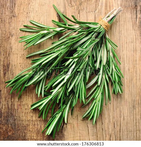 Twigs of rosemary on wooden texture - stock photo