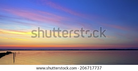 Twilight at the beach as the sun goes down and the sky glows. - stock photo