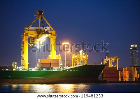 twilight Container Cargo freight ship with working crane bridge in shipyard at dusk for Logistic Import Export background - stock photo