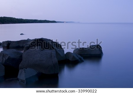 Twilight, glass water, and stone on the North Shore of Lake Superior - stock photo