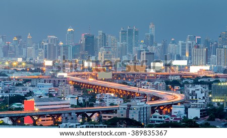 Twilight, highway curved and city downtown background - stock photo