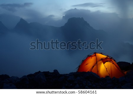 Twilight in the mountains and orange lighting tent - stock photo