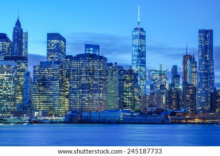 Twilight over the New York City skyline and the financial district as seen from the East River - stock photo