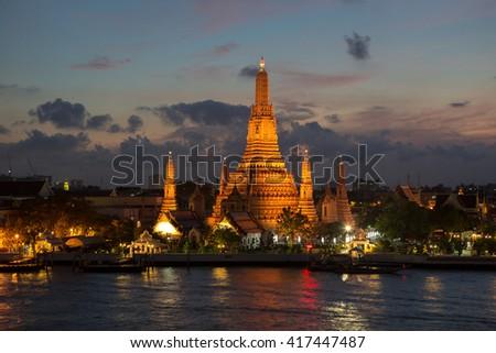 Twilight view of Wat Arun across Chao Phraya River during sunset in Bangkok, Thailand - stock photo