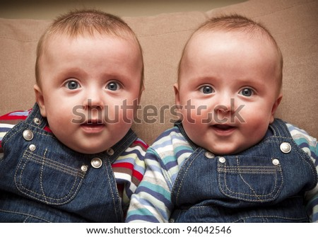 Twin boys in overalls looking at the camera - stock photo