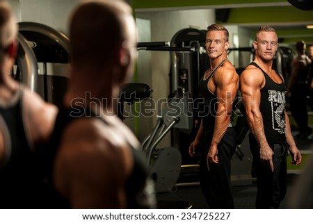 Twin brothers looking in mirror after body building workout - stock photo