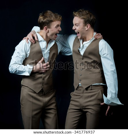 Twin brothers. Two young and attractive twin brothers are standing in formal suits on black background and giving a true and bright emotion. Fashion concept on black background - stock photo