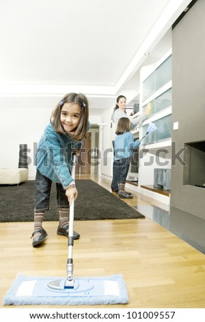 Twin daughters and mum cleaning their home's living room. - stock photo