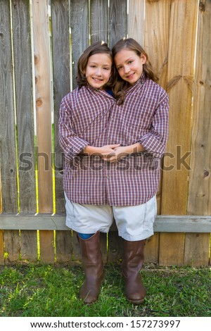 twin girls fancy dressed up pretending be siamese with his father shirt - stock photo