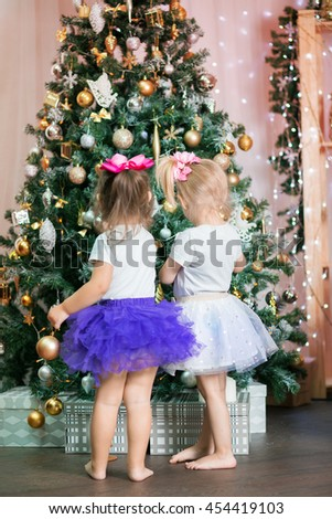 twin little girls in skirts tutu near a Christmas tree with a funny Christmas balls decorate the new year  tree stand back - stock photo