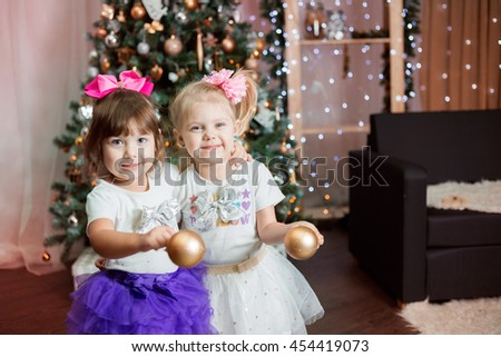 twin little girls in skirts tutu near a Christmas tree with Christmas balls cheerful smile - stock photo