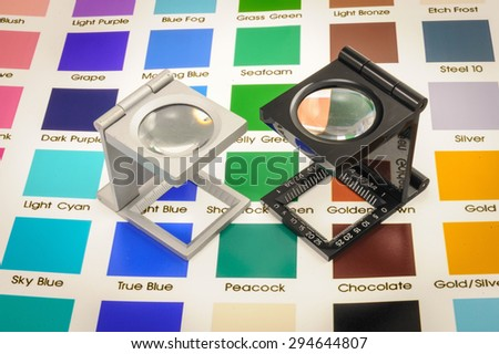 Twin magnifier loupes color management on color chart. - stock photo
