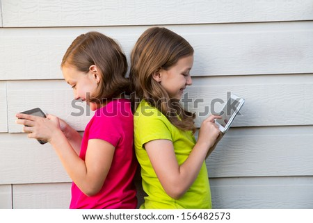 Twin sister girls playing with tablet pc happy on white wall leaning on her back - stock photo