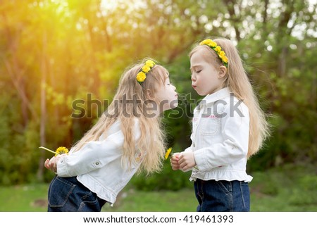Twin sisters cheerfully play with  dandelionson a spring glade - stock photo