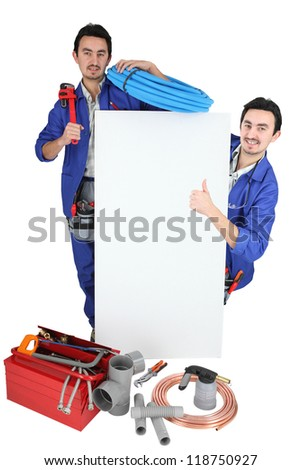 Twin tradesmen standing around a blank sign - stock photo