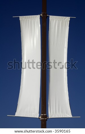 Twin white banners on pole in sunlight - add your own message - stock photo