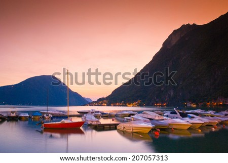 Twinkling village lights, sunset mountain backdrop and glassy waters on the beautiful Lake Lugano Italy. - stock photo