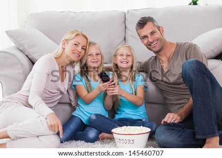 Twins and parents eating popcorn and watching television sitting on a carpet - stock photo