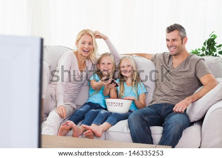 Twins and parents watching television sitting on a couch - stock photo